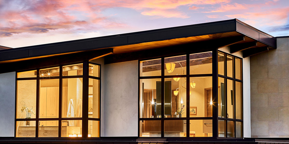 Exterior view of master bath lit up at dusk. Architecture by KGA.
