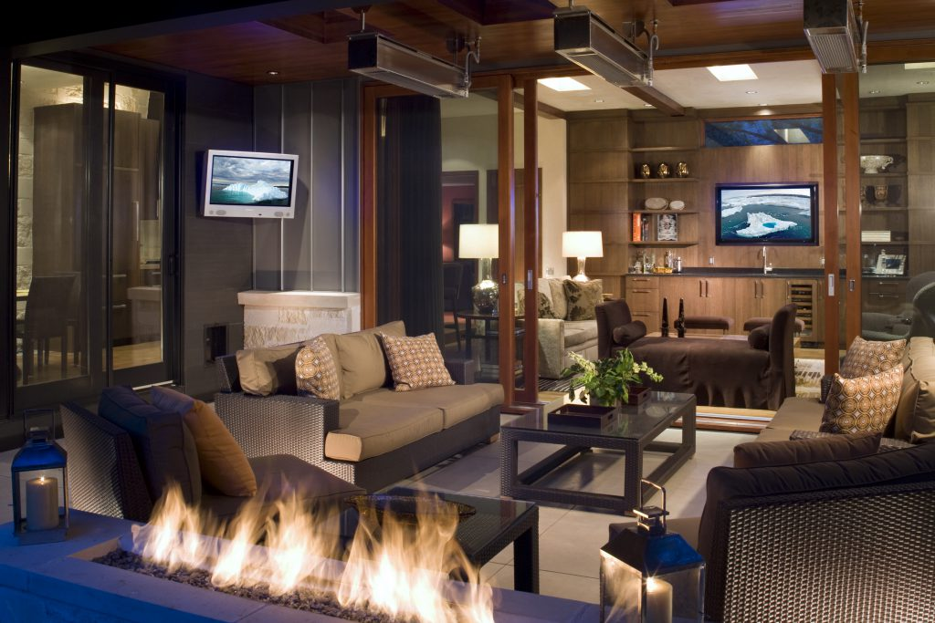 This remodeled Aspen home blurs the lines between inside and outside with indoor/outdoor living spaces and televisions. Photo: Harrison Home Systems.