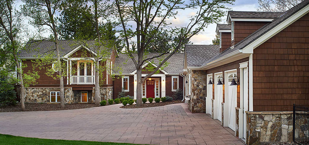 Brown Shingle Style home with white garage doors