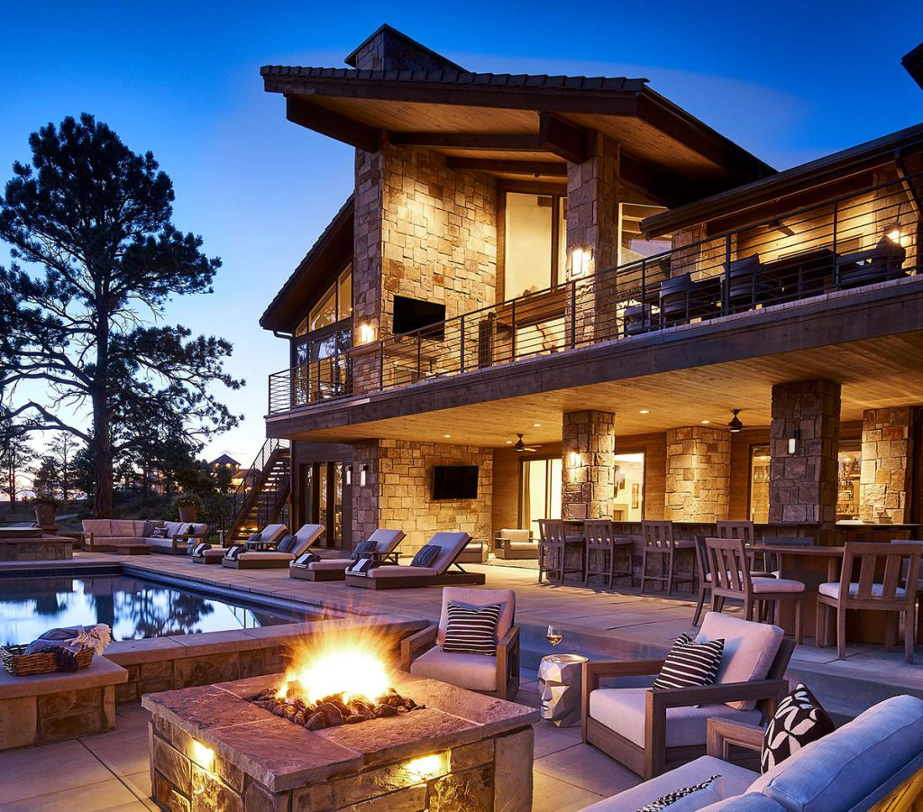 Rear elevation of custom home with pool at dusk in the Colorado Golf Club