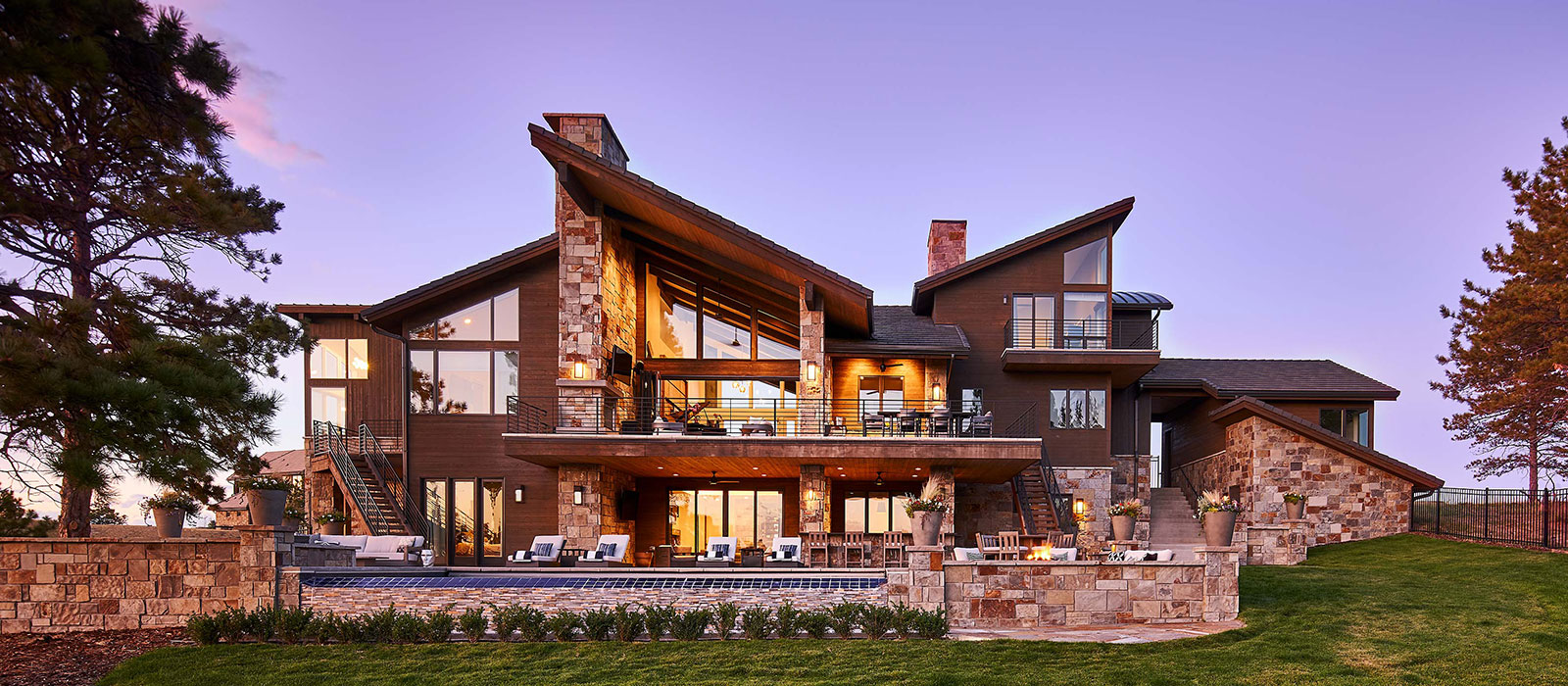 Rear elevation of modern rustic custom home with slanting roof lines in Colorado Golf Club