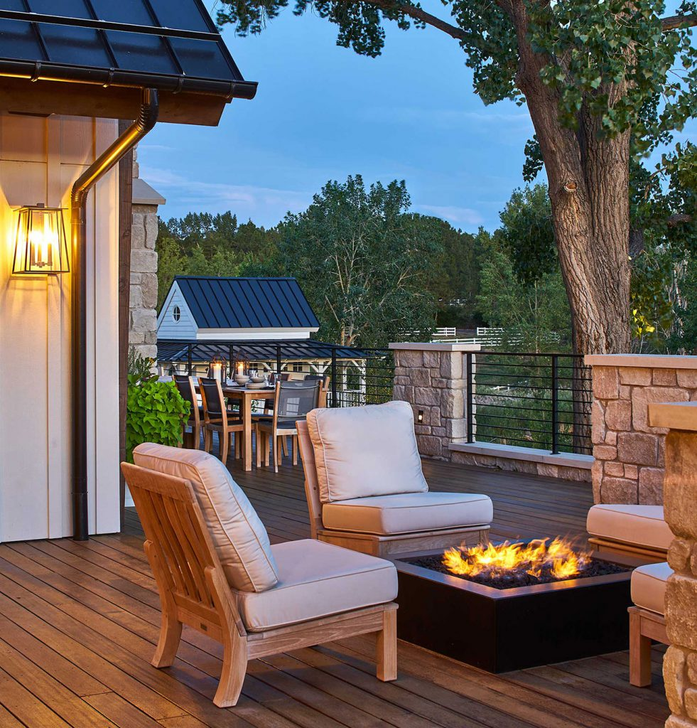 Wrap around deck with firepit and outdoor dining in modern farmhouse remodel by KGA