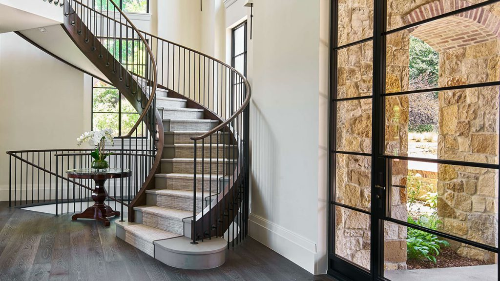 Front entry with curved floating staircase and lots of windows to let in natural light, which helps with health and wellness at home.