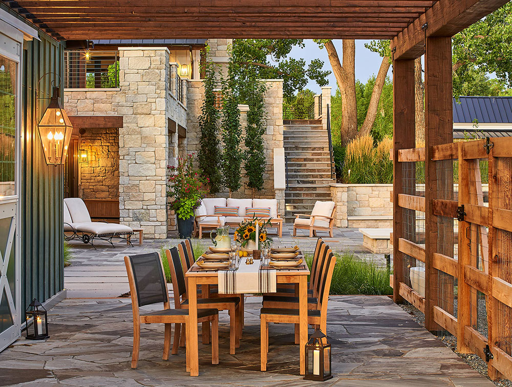 This luxury outdoor living space features a patio between the small, detached barn and fenced in raised garden beds.